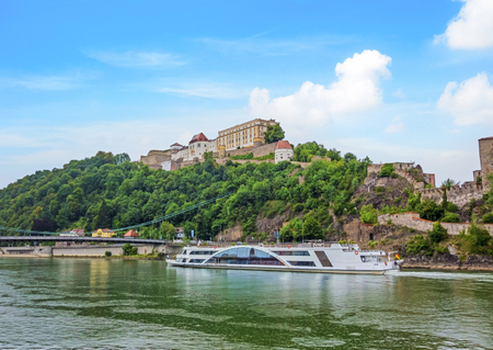 stronghold: Veste Oberhaus, historical stronghold of the old historical city of Passau, a famous tourist spot - view from the river Donau with cruising passenger ship