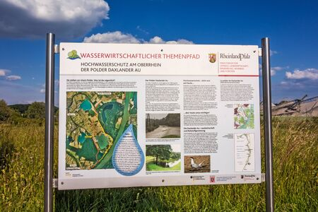 au: Hagenbach, Germany - May 31, 2014: Flood defence information sign of environment department of Rhineland-Palatinate - polder Daxlander Au protects the Upper Rhine region