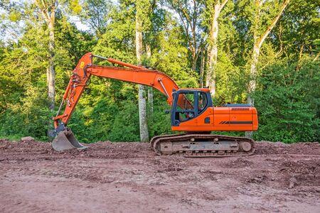crawler: Orange crawler excavator standing in the woods