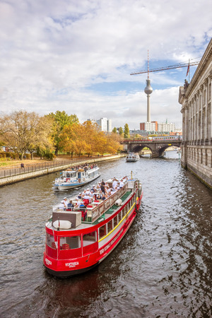 tv tower: Berlin, Germany - October 26, 2013: Tourist boats on the Spree river - famous TV tower on Alexanderplatz square in the background.