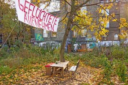 inscribed: Berlin, Germany - October 26, 2013: Banner inscribed with Admit Refugees (Gefluechtete aufnehmen) - in a less wealthier neighborhood of Berlin, Germany. Editorial