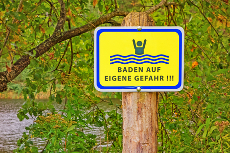 own: Sign at a lake labeled with Baden auf eigene Gefahr (swimming at own risk)