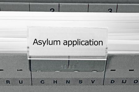 asylum: grey hanging file folder labeled with asylum application Stock Photo