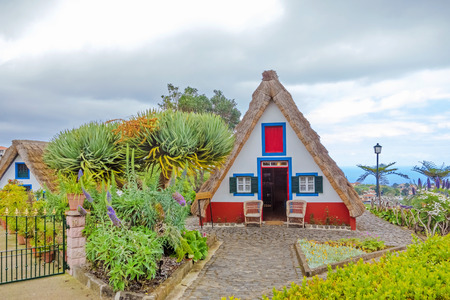Santana, Portugal - June 7, 2013: Flower's related craft souvenir shop built like a typical triangular house, Island of Madeira.