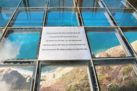 steep cliff sign: Camara de Lobos, Portugal - June 1, 2013: Skywalk at Cabo Girao, Madeira. View down to the atlantic ocean. The glass platform is 580 meters high.