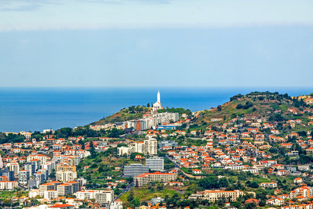 Funchal, Madeira - June 7, 2013: Sao Martinho church and the hilltops overlooking the southern coast of Madeira