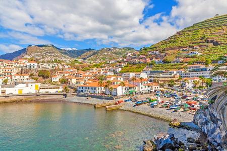 case colorate: Camara de Lobos, Madeira - 8 Giugno 2013: porto con le barche da pesca. Il villaggio è tipico per il suo essiccamento squalo gatto sotto il sole.