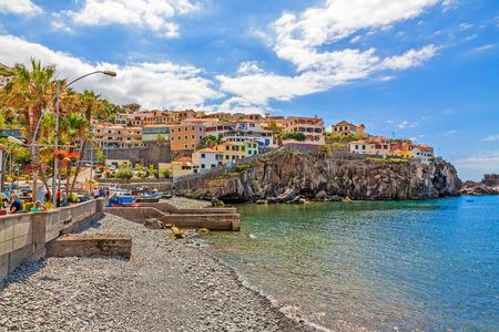 case colorate: Camara de Lobos, Madeira - 8 Giugno, 2013: Città Camara de Lobos, Madeira con barche da pesca. Il pittoresco villaggio di pescatori è famoso per il suo ex ospite Winston Churchill.