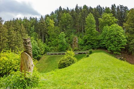swabian: Wental valley reservoir dam - forest  trees in background, carved owl in foreground - Swabian Alps (Schwaebische Alb)