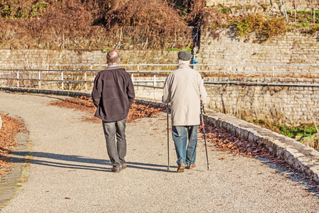 view from behind: Two older people walking - one with walking sticks. View from behind.
