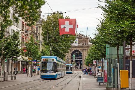 Zurich, Switzerland - June 10, 2017: Shopping promenade called Bahnhofstrasse, inner city of Zurich. Tram / train with swiss flag in front.