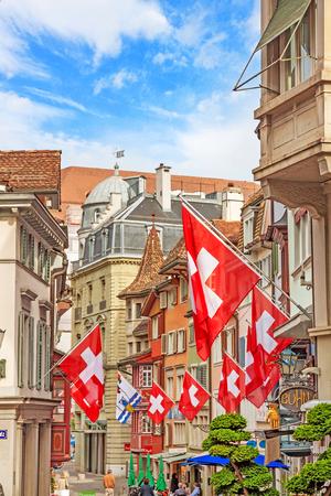Zurich, Switzerland - June 10, 2017: Street Augustinergasse in Zuerich, Lindenhof quarter with swiss flags.