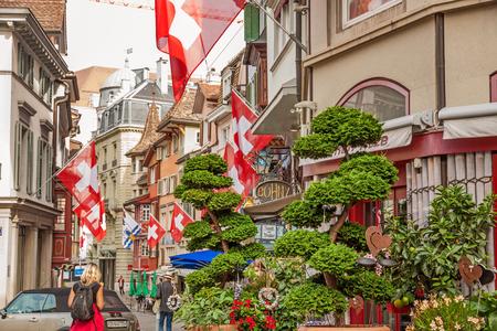 first day: Zurich, Switzerland - June 10, 2017: Street Augustinergasse in Zuerich, Lindenhof quarter with swiss flags.