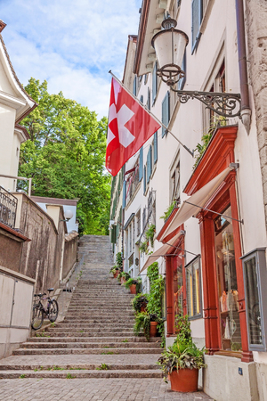 Beautiful view of historic city center of Zurich with Swiss flags at buildings on a sunny day in summer, Switzerland Editorial