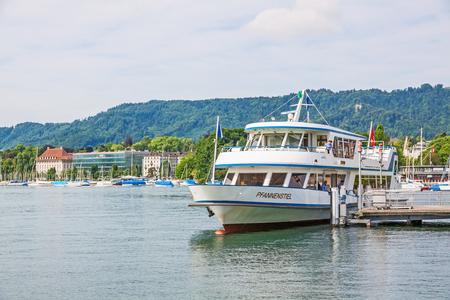 Zurich, Switzerland - June 10, 2017: Excursion boat Pfannenstiel arriving at shipping pier Burkliplatz. Western bank of Lake Zurich, Mythenquai  Enge in background. Editorial