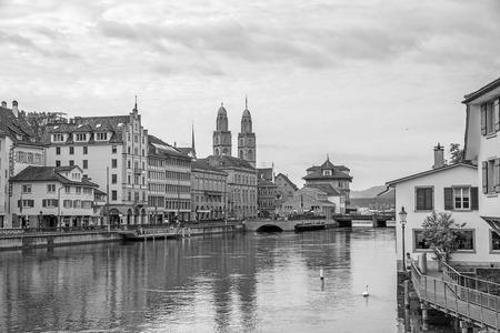 Downtown view of Zurich from bridge Rudolf-Brun-Brucke, Grossmunster, town hall and river Limmat in front - black and white.