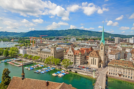 Aerial view of historic Zurich city center with famous Fraumunster Church, townhouse and river Limmat at Lake Zurich from Grossmunster Church on a sunny day with clouds in summer, Canton of Zurich, Switzerland