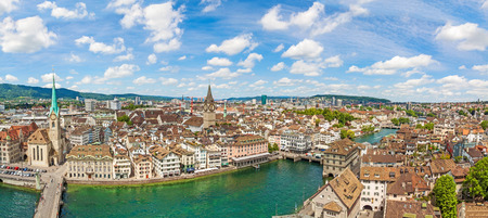 Zurich city center panorama with famous Fraumunster church, St. Peter church and river Limmat - view from Grossmunster church on a sunny day with clouds in summer, Canton of Zurich, Switzerland