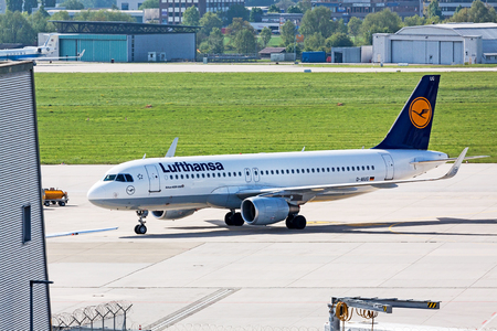 despatch: Stuttgart, Germany - May 06, 2017: Airbus A320 airplane from Lufthansa at ground (airport Stuttgart) on its way to parking position - green meadow and hangar in background Editorial