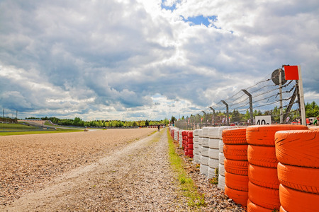 Nurburg, Germany - May 20, 2017: Race track Nurburgring - gravel bed beside speedway with orange, white tyre stack