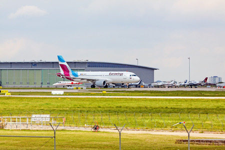 Stuttgart, Germany - April 29, 2017: Airbus A319 airplane from Eurowings at ground (airport Stuttgart) on its way to take off - green meadow with fence in front, hangar in background