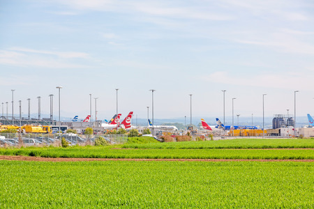despatch: Leinfelden-Echterdingen, Germany - May 06, 2017: Airport Stuttgart, planes of different airlines in parking position in front of terminal, green field in foreground