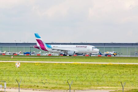 despatch: Stuttgart, Germany - April 29, 2017: Airbus A319 airplane from Eurowings at ground (airport Stuttgart) on its way to take off - green meadow with fence in front, hangar in background