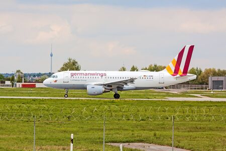 despatch: Stuttgart, Germany - April 29, 2017: Airbus A319 airplane from Germanwings  Lufthansa Group at ground (airport Stuttgart) after landing - green meadow with fence in front, tv tower in background