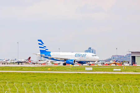 despatch: Stuttgart, Germany - April 29, 2017: Airbus airplane from Ellinair at ground (airport Stuttgart) before take off - green meadow with fence in front