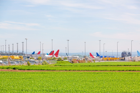 despatch: Airport Stuttgart, planes of different airlines in parking position in front of terminal, green field in foreground