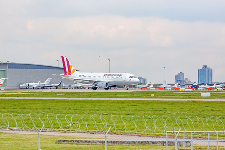 despatch: Stuttgart, Germany - April 29, 2017: Airbus A319 airplane from Germanwings  Lufthansa Group at ground (airport Stuttgart) on its way to take off - green meadow with fence in front, hangar in background Editorial