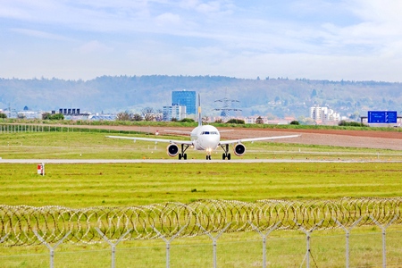 despatch: Airplane at ground on its way to runway before takeoff - green meadow with fence in front