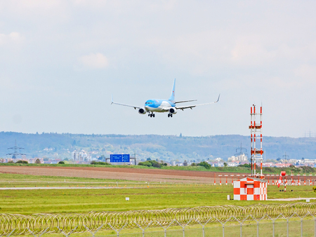 despatch: Stuttgart, Germany - April 29, 2017: Airbus airplane A320 from TUIfly on landing approach to airport Stuttgart - green meadow with weather station in front