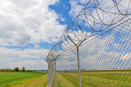 fence with barbed wire, green landscape and blue sky with clouds