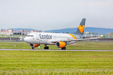 despatch: Stuttgart, Germany - April 29, 2017: Airbus airplane A320 from Condor at ground (airport Stuttgart) before takeoff - green meadow with fence in front