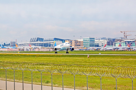 despatch: Stuttgart, Germany - April 29, 2017: Airbus airplane A320 from Condor at takeoff from runway - airport Stuttgart terminal in background - green meadow with fence in front
