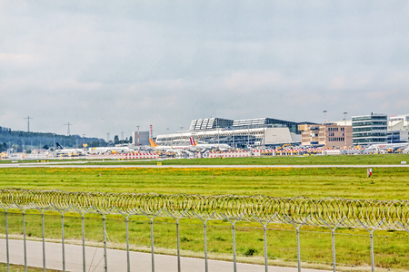 despatch: Stuttgart, Germany - May 06, 2017: Airport Stuttgart (Manfred-Rommel-Flughafen), Terminal, exterior view with airplanes in parking position, runway in front