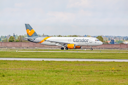 despatch: Stuttgart, Germany - April 29, 2017: Airbus airplane A320 from Condor at ground (airport Stuttgart) before take off - green meadow with fence in front