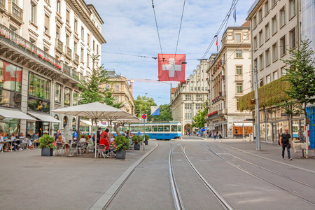 Shopping promenade called Bahnhofstrasse, inner city of Zurich. Cafe with people sitting in front, tram / train in background, with swiss flag. Stockfoto