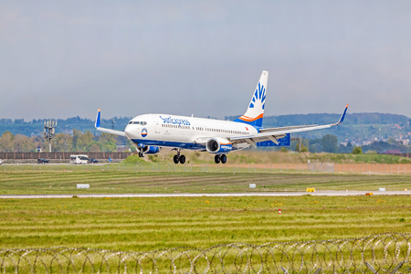 airstrip: Stuttgart, Germany - April 29, 2017: Boeing 737 airplane from SunExpress airline on landing approach to airport Stuttgart - green meadow with fence in front