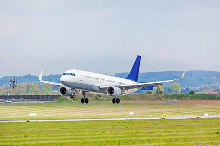 despatch: Airplane with blue tail fin on landing approach at airport - runway and green meadow in front