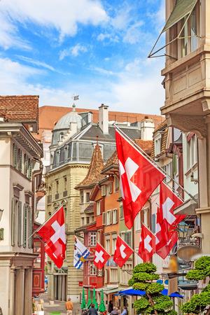 Street Augustinergasse in Zuerich, Lindenhof quarter with swiss flags, Switzerland. Stock Photo