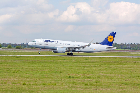 despatch: Stuttgart, Germany - April 29, 2017: Airbus airplane A320 200 from Lufthansa on landing approach at airport Stuttgart - runway and green meadow in front