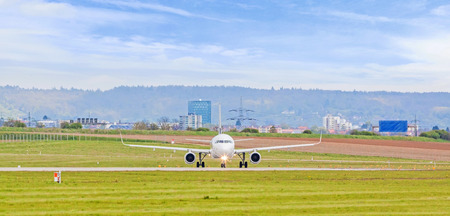 despatch: Airplane at ground on its way to runway before takeoff - green meadow in front - panorama
