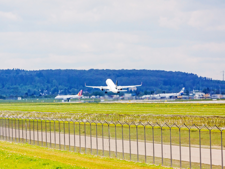 despatch: Stuttgart, Germany - April 29, 2017: Airbus airplane A320 from Turkish Airlines  Star Alliance after takeoff (airport Stuttgart) - green meadow with fence in front Editorial