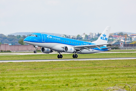 despatch: Stuttgart, Germany - April 29, 2017: Airplane Embraer ERJ-175 from KLM cityhopper during landing - green meadow in front
