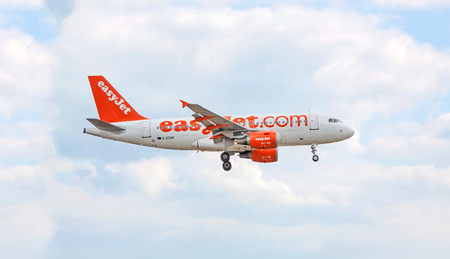 despatch: Stuttgart, Germany - April 29, 2017: Airbus airplane A319-100 from easyJet landing approach  after takeoff - airport Stuttgart, sky with clouds in background