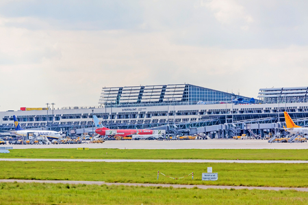 despatch: Stuttgart, Germany - May 06, 2017: Airport Stuttgart, Terminal with airplanes in parking position, exterior view with runway and green meadow in foreground