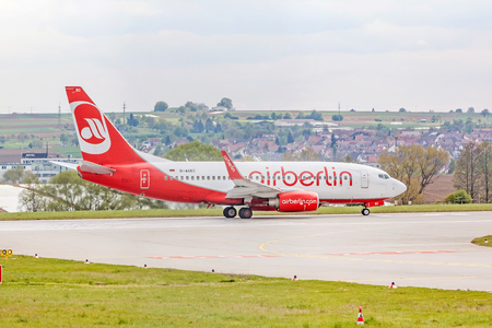 despatch: Stuttgart, Germany - April 29, 2017: Boeing airplane 737 from Air Berlin at ground (airport Stuttgart) before takeoff - runway and green meadow in front