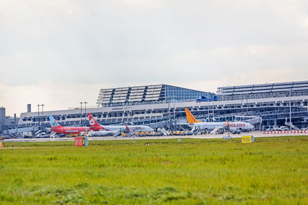 despatch: Stuttgart, Germany - May 06, 2017: Airport Stuttgart, Terminal with airplanes in parking position, exterior view with runway and green meadow in front Editorial